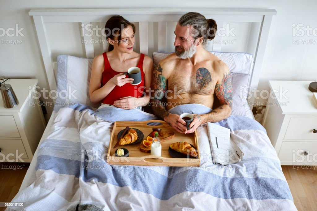 Pregnant couple having bed tea and breakfast stock photo