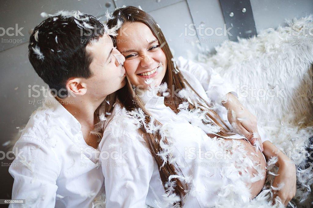 Pregnant couple having fun, pillow fight stock photo
