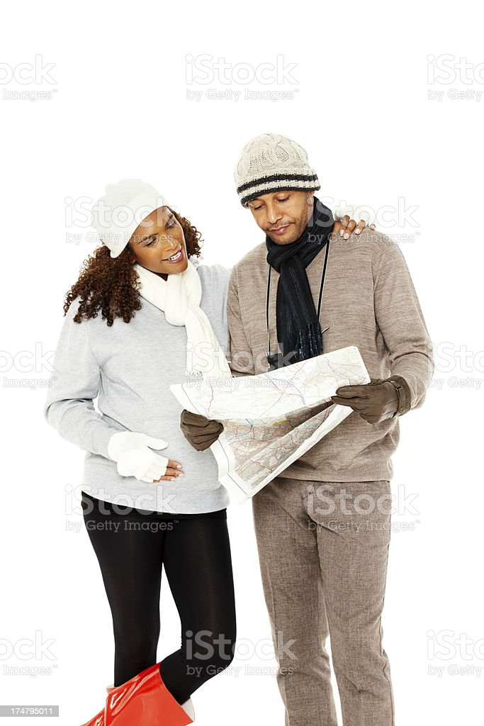 Pregnant couple in winter clothing holding a map royalty-free stock photo