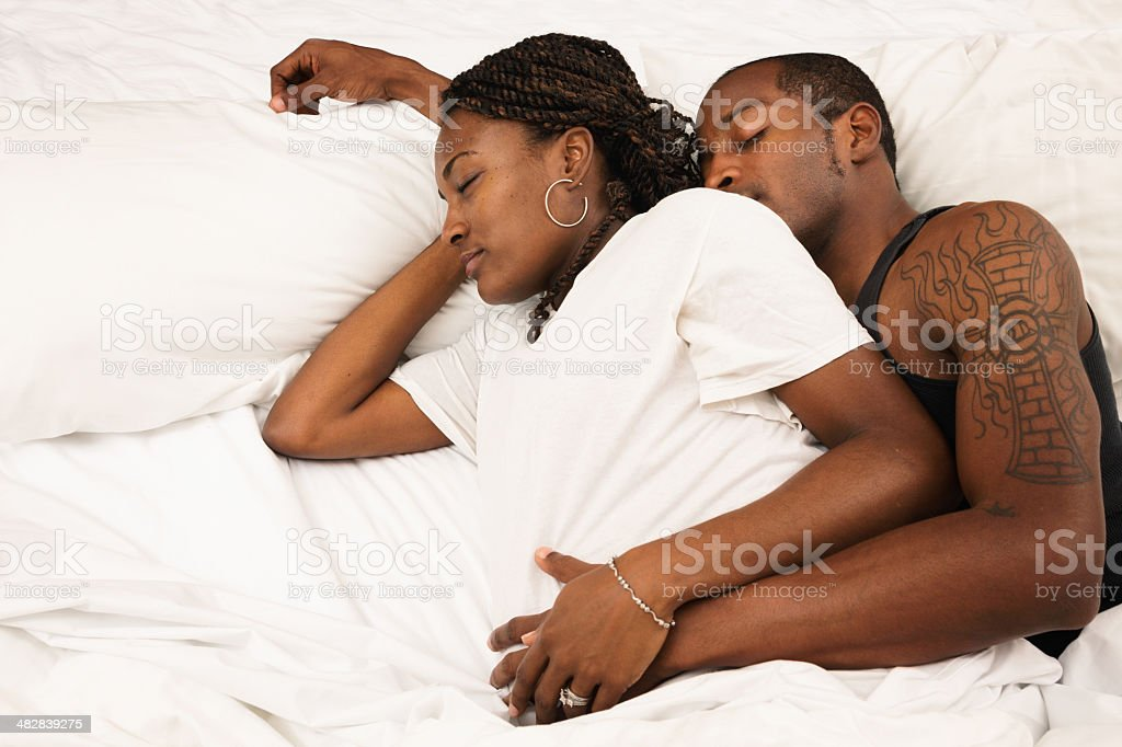 Pregnant couple napping spooning in bed profile royalty-free stock photo