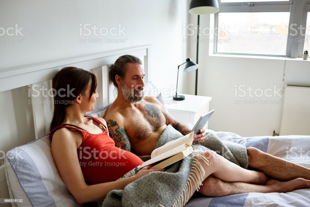 Pregnant couple on bed with book and digital tablet stock photo