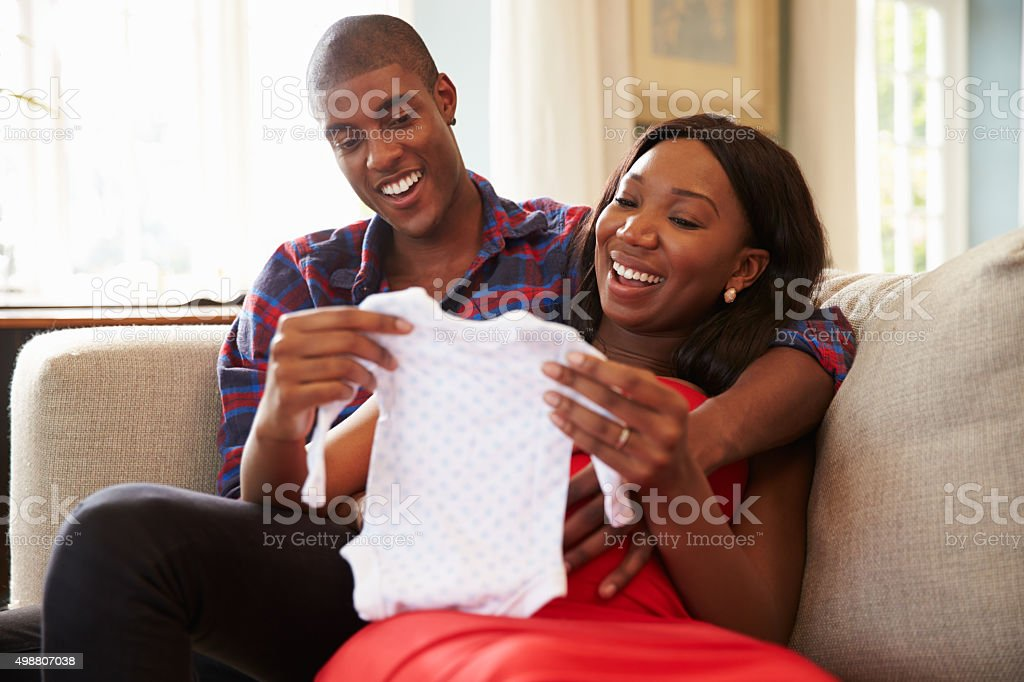 Pregnant Couple On Sofa At Home Looking At Baby Clothes stock photo