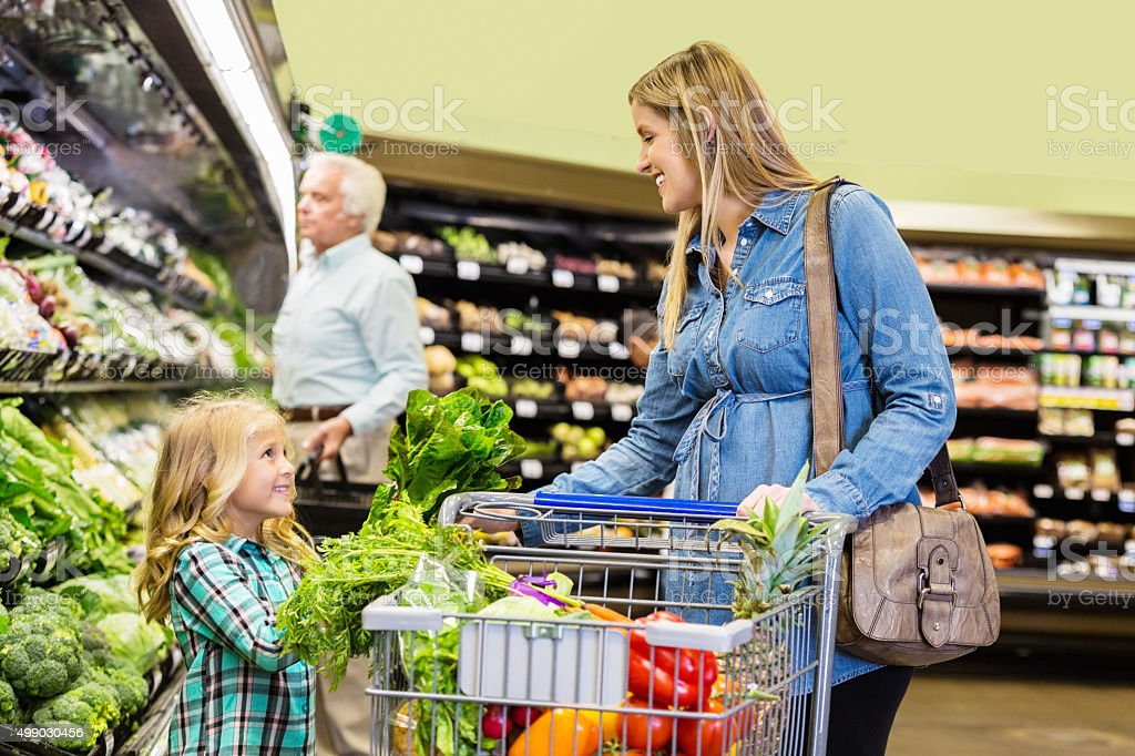 Pregnant customer shopping for groceries with daughter in supermarket stock photo