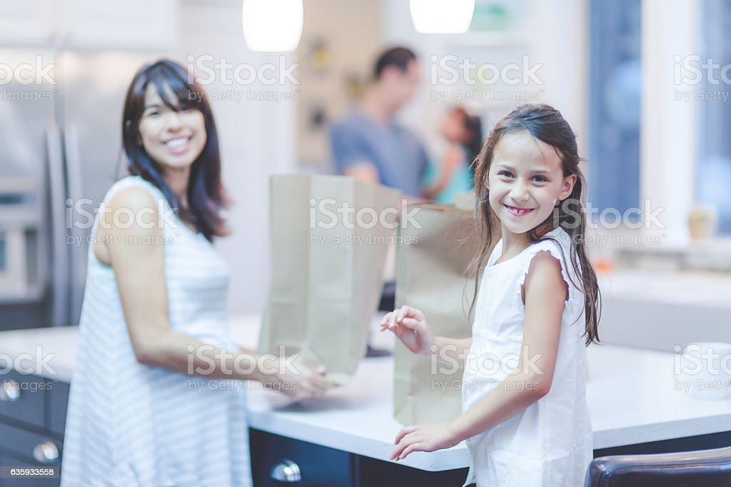 Pregnant ethnic mother putting groceries away and stock photo