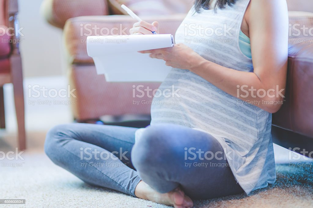 Pregnant ethnic mother writing out to do lists while stock photo