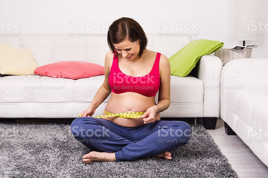 Pregnant happy smiling woman measuring waist stock photo
