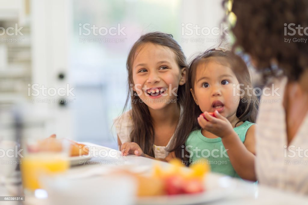 Pregnant Hawaiian Couple and Young Daughter eating dinner at table stock photo