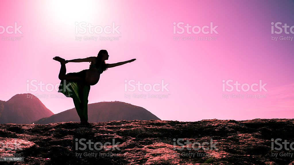 Pregnant lady on a Standing Bow Pose - Yoga stock photo