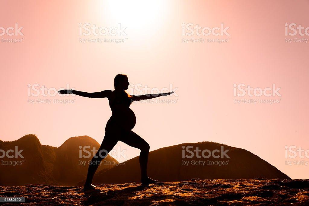 Pregnant lady on a warrior II yoga pose stock photo