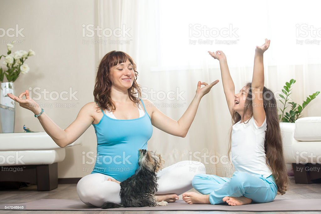 Pregnant mother and kid girl meditating at home stock photo