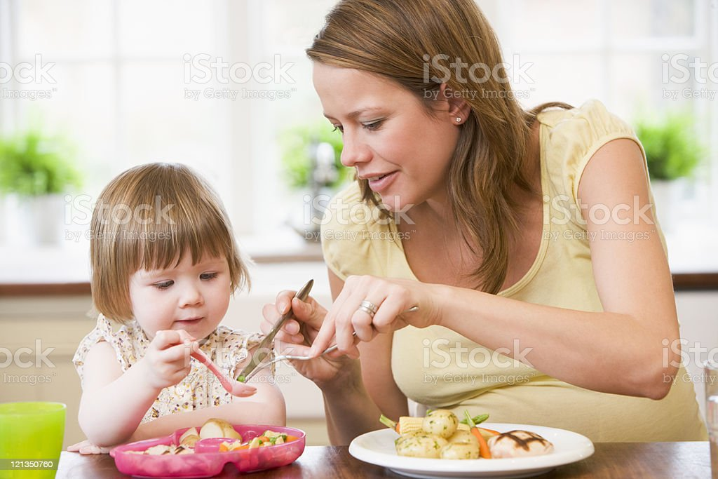 Pregnant mother in kitchen eating meal helping daughter eat royalty-free stock photo