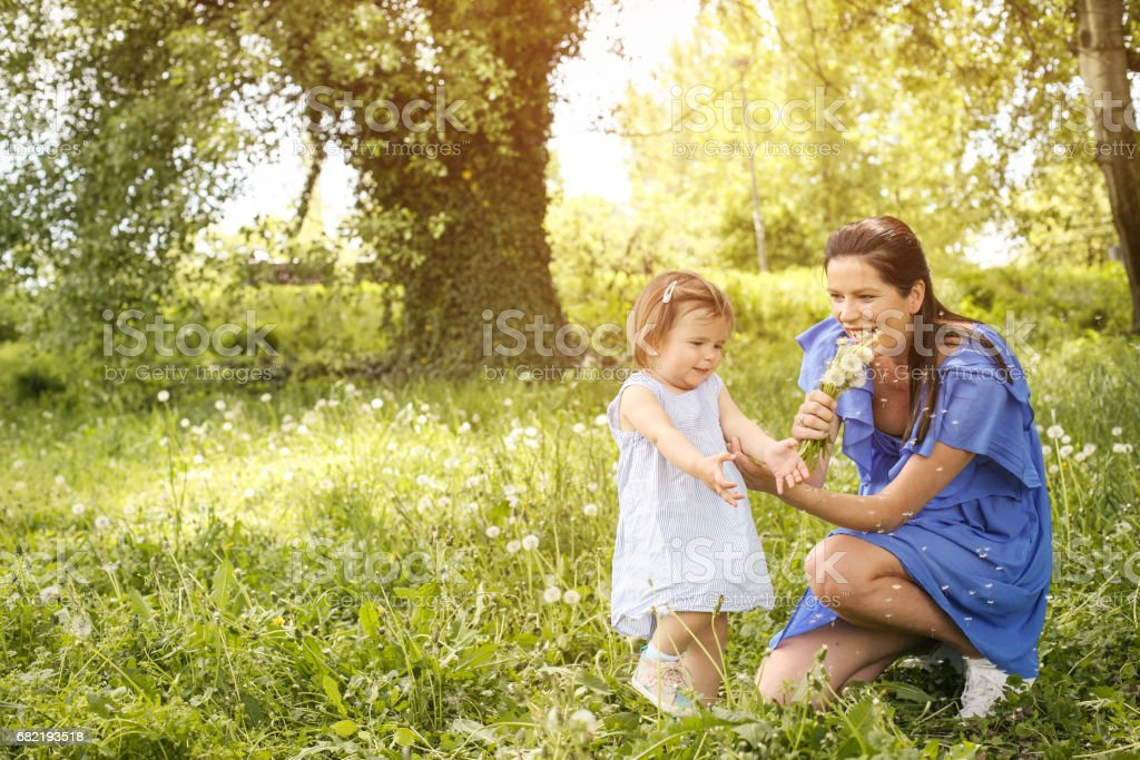 Pregnant mother playing with little daughter in park. Mother and daughter in nature. stock photo