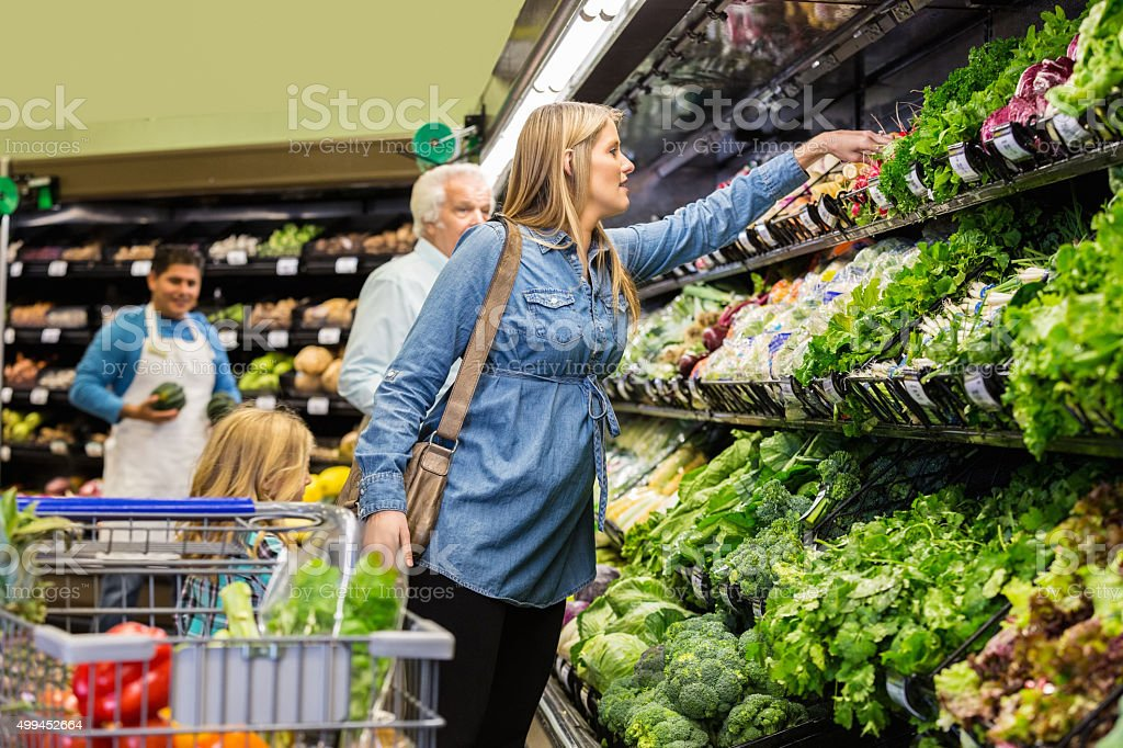 Pregnant mother shopping for produce in grocery store with daughter stock photo