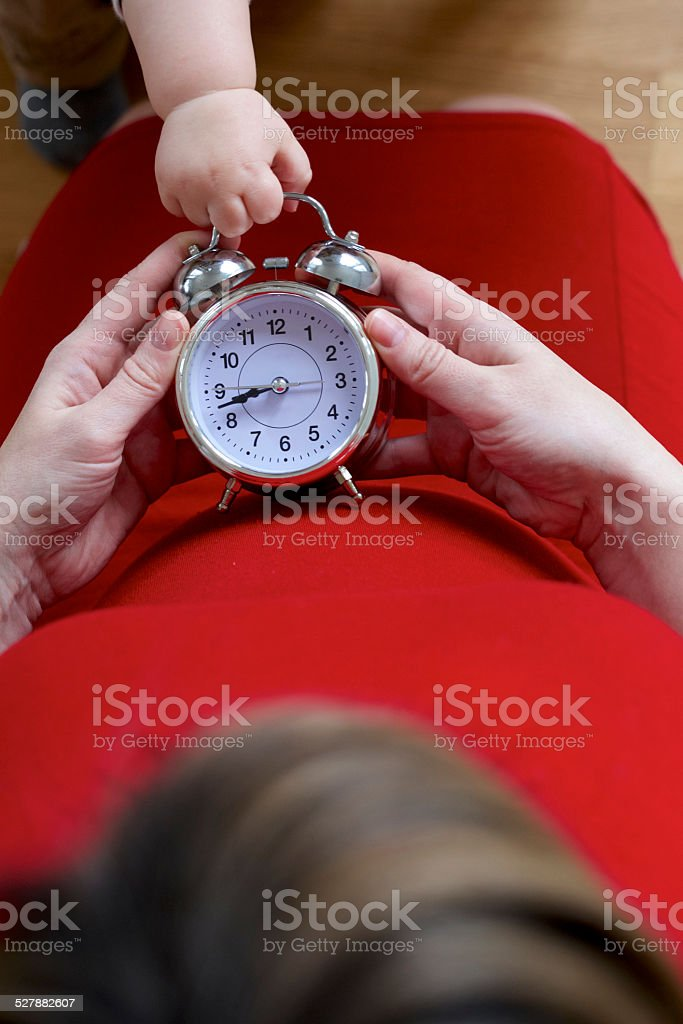 Pregnant mother with her impatient toddler stock photo