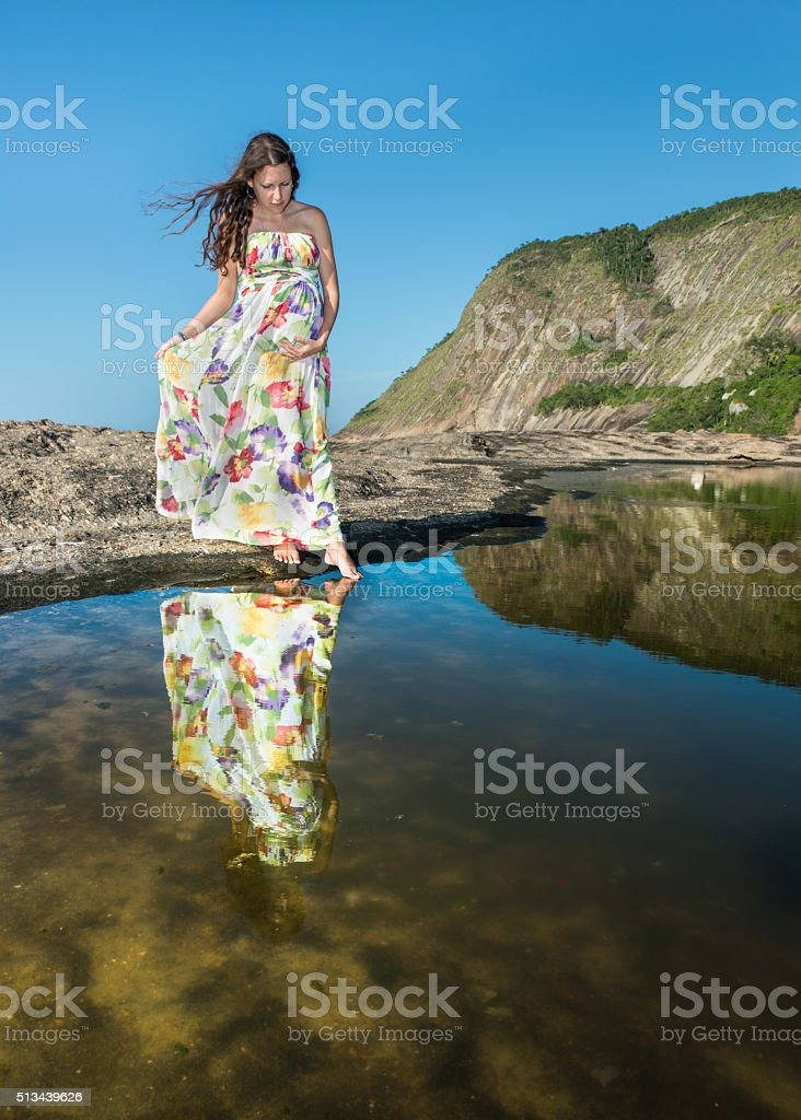 Pregnant on a floral dress looking at her reflection royalty-free stock photo