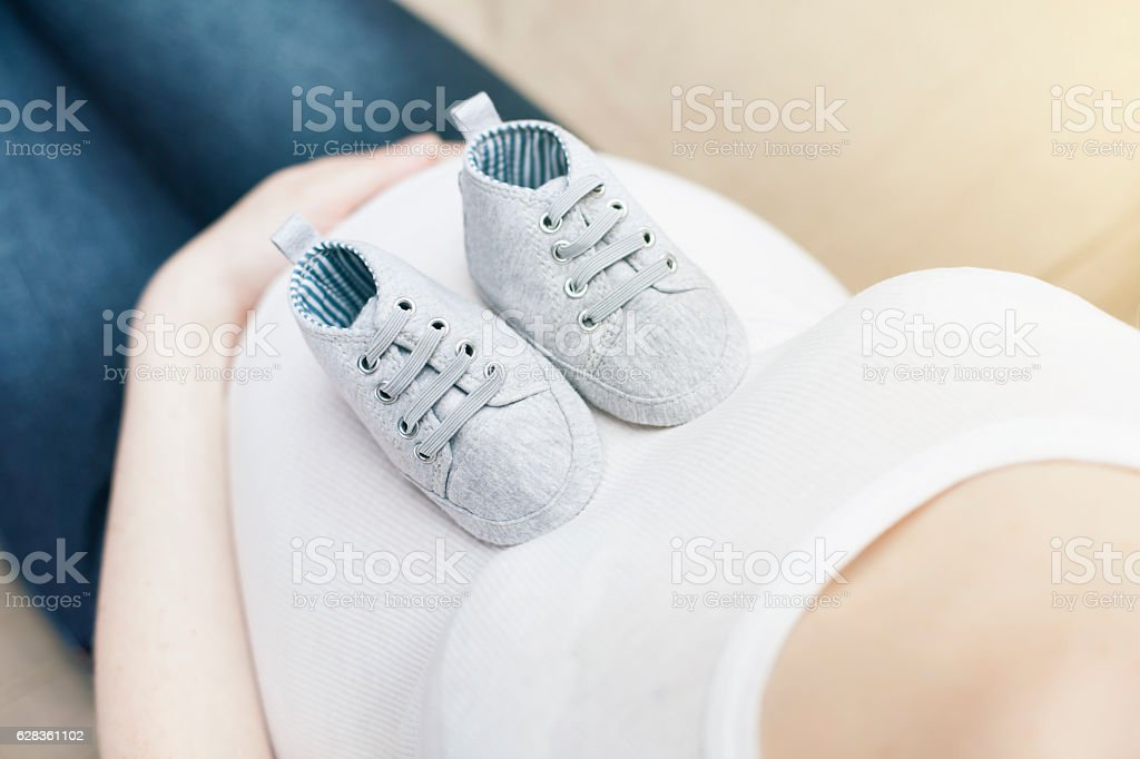 Pregnant woman and baby shoes stock photo