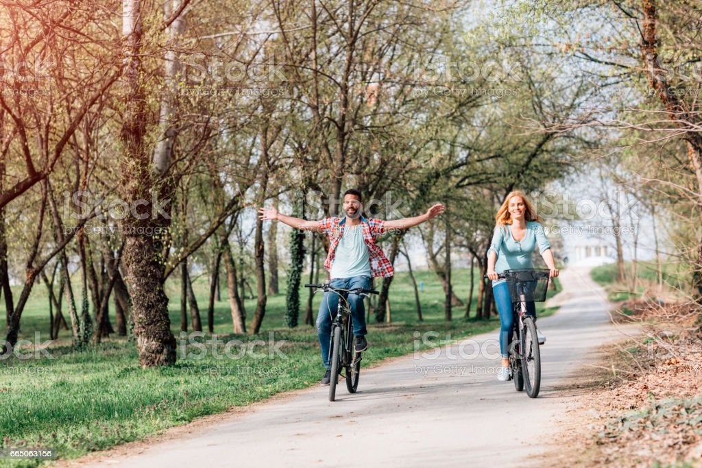 Pregnant Woman and Her Husband Riding Bicycles stock photo