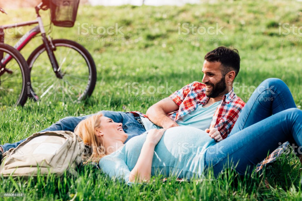 Pregnant Woman and her Partner In Park stock photo