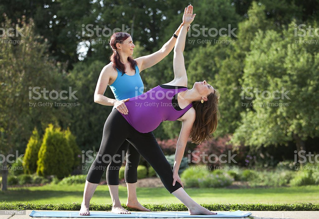 Pregnant Woman and Instructor Practicing Yoga Outdoors. stock photo