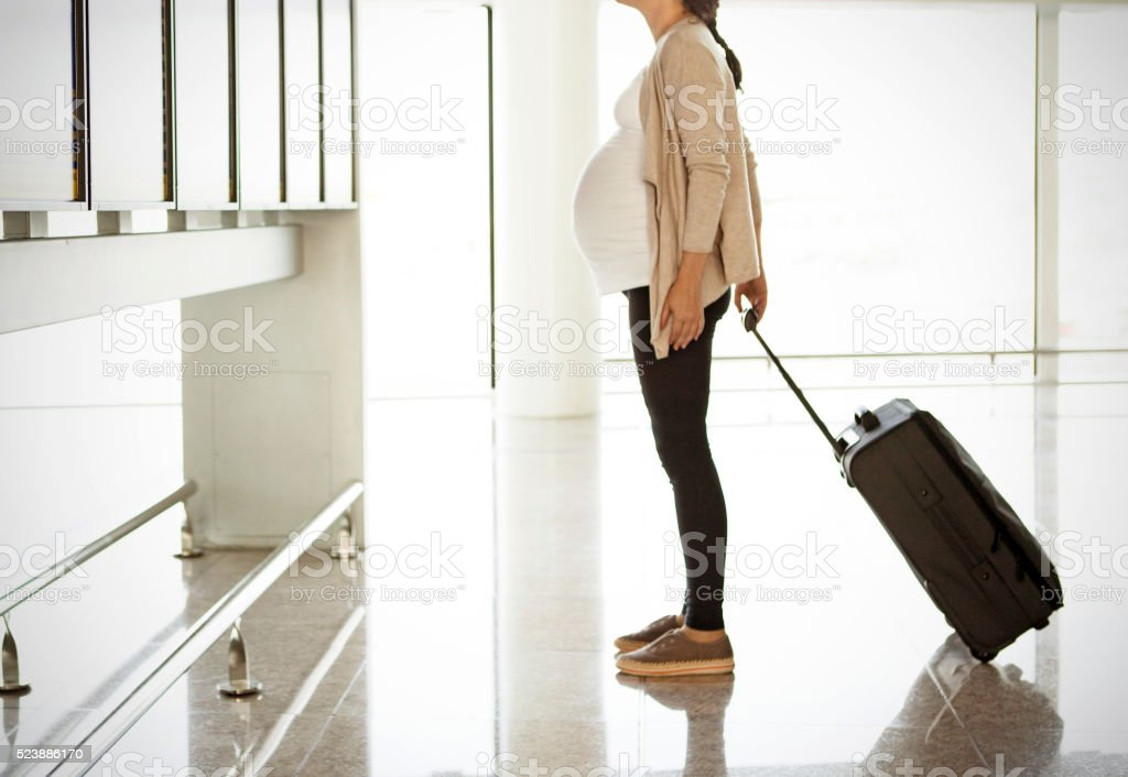 Pregnant woman at the airport stock photo