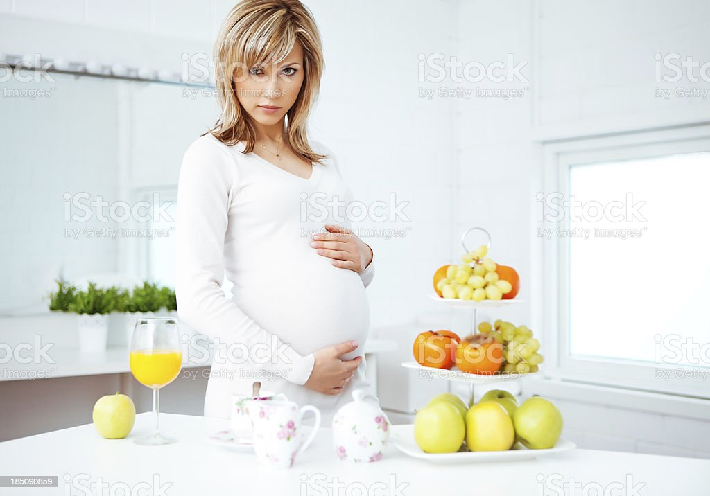 pregnant woman at the kitchen touching her belly stock photo