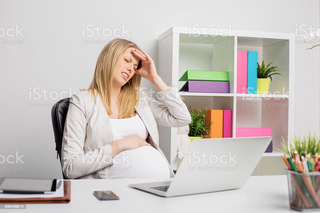 Pregnant woman at the office having headache stock photo