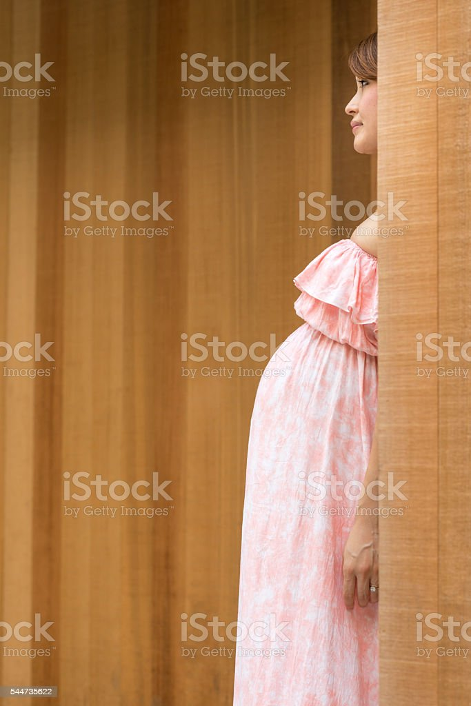 Pregnant woman behind corner. stock photo