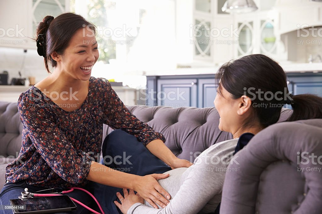 Pregnant Woman Being Examined At Home By Midwife royalty-free stock photo