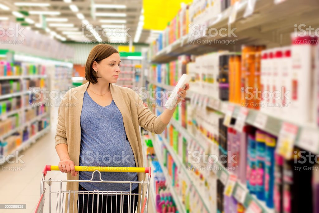 pregnant woman buying shampoo stock photo