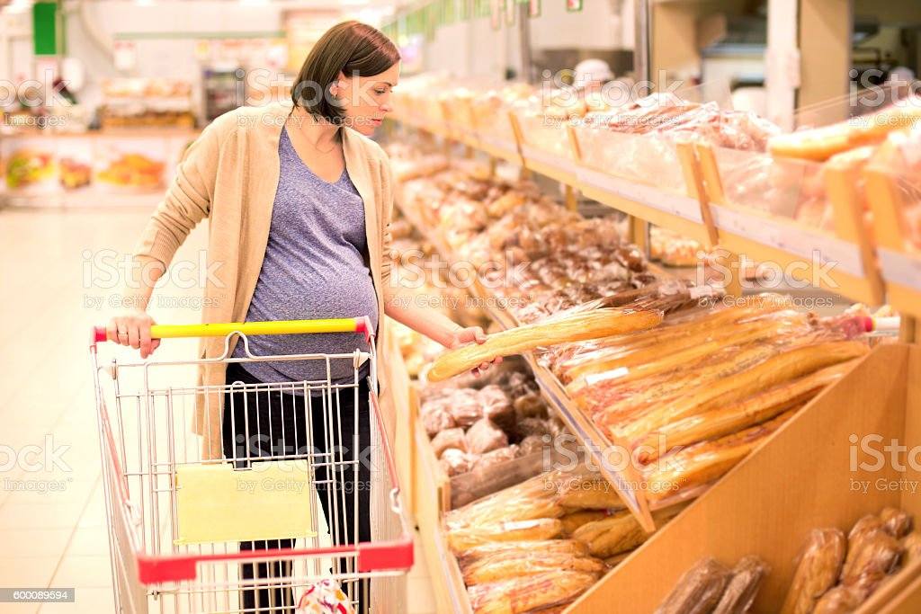 pregnant woman buys bread at the supermarket stock photo