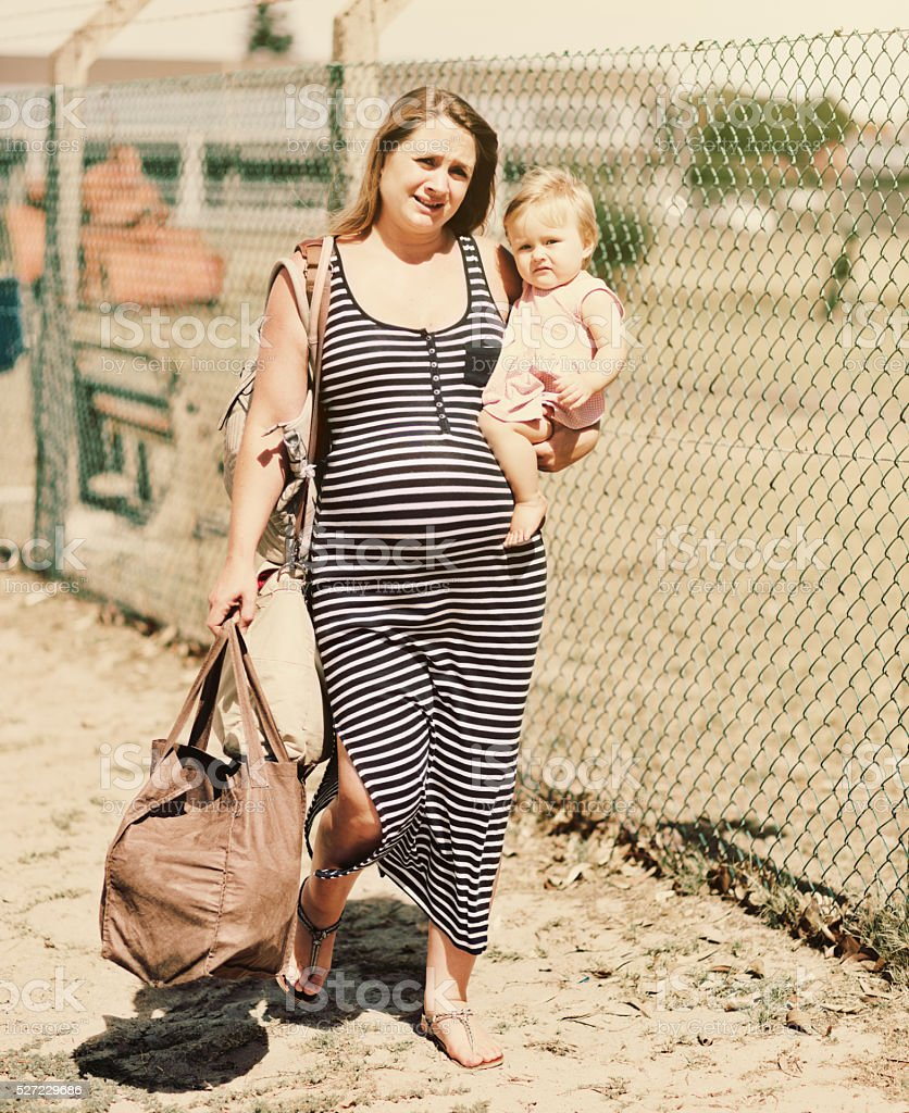Pregnant woman carrying toddler through poor area, depressed and exhausted stock photo