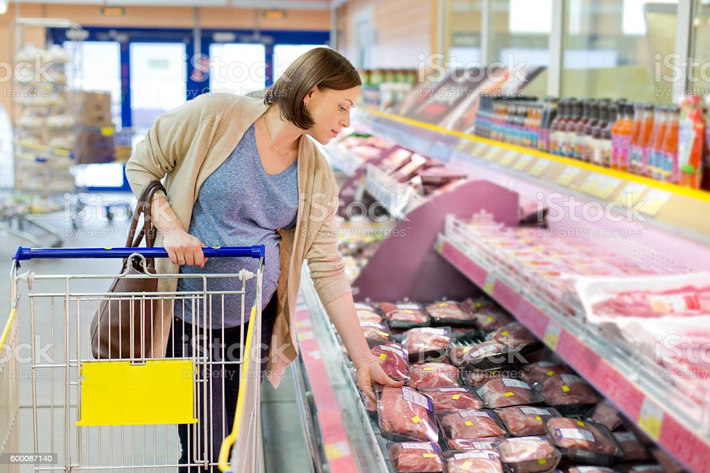 pregnant woman chooses meat in the store stock photo