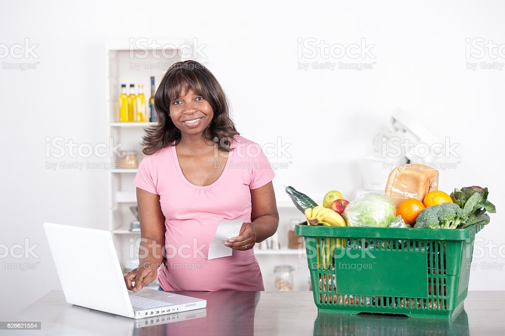 Pregnant Woman Comparing A Receipt With An Online Order Statement stock photo