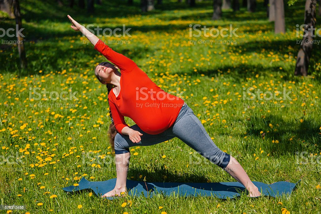Pregnant woman doing asana Utthita parsvakonasana outdoors stock photo