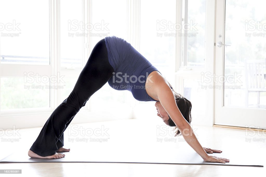 Pregnant Woman Doing Downward-Facing Dog Yoga Pose stock photo
