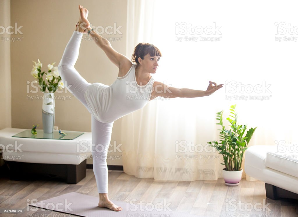 Pregnant woman doing Lord of the Dance yoga pose home stock photo