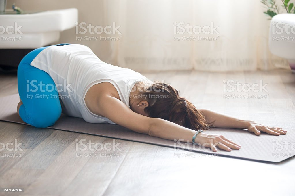 Pregnant woman doing prenatal Child Yoga Pose at home stock photo