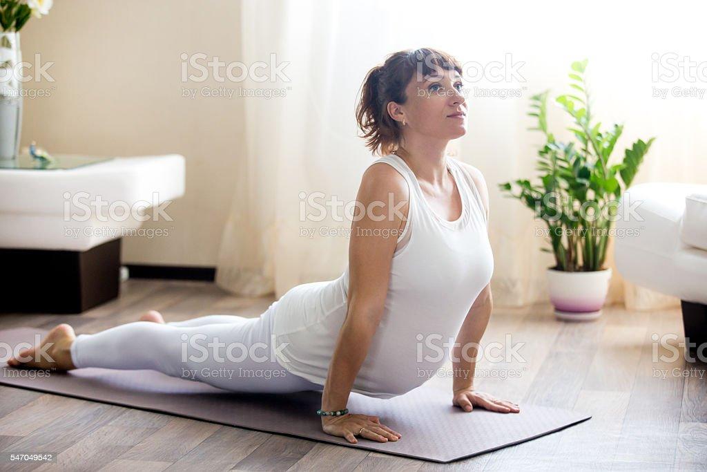 Pregnant woman doing upward facing dog yoga pose at home stock photo