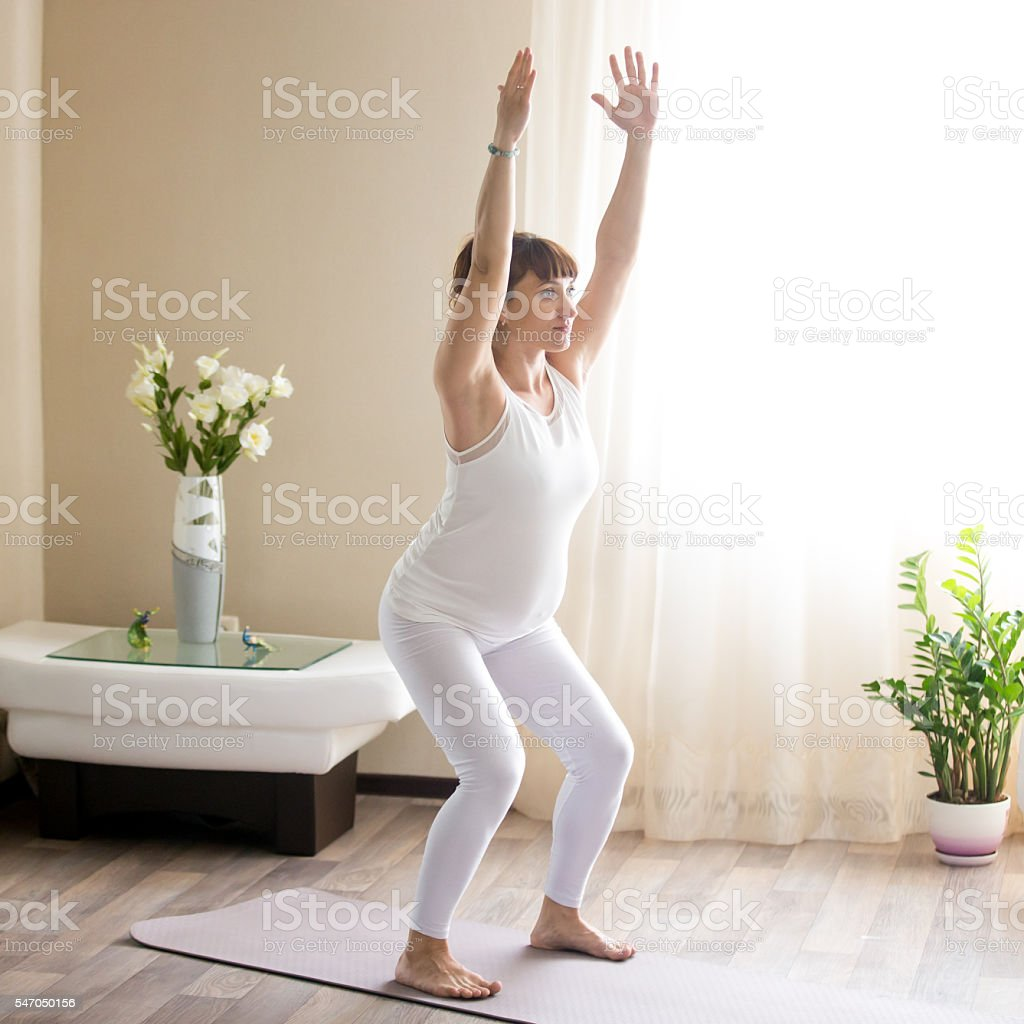 Pregnant woman doing Utkatasana,  Chair yoga pose at home stock photo