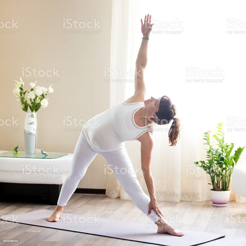 Pregnant woman doing Utthita Trikonasana yoga pose at home stock photo