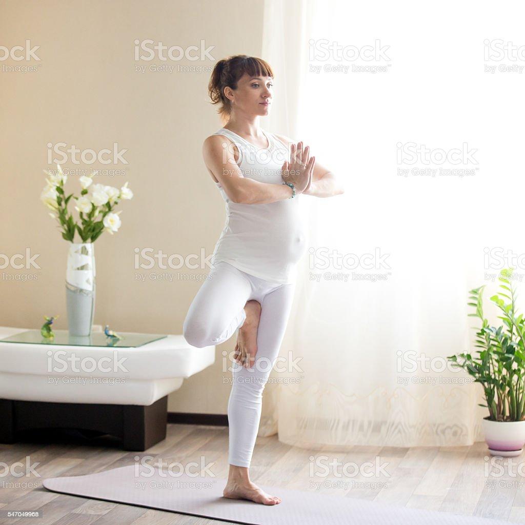 Pregnant woman doing Vrksasana yoga pose at home stock photo