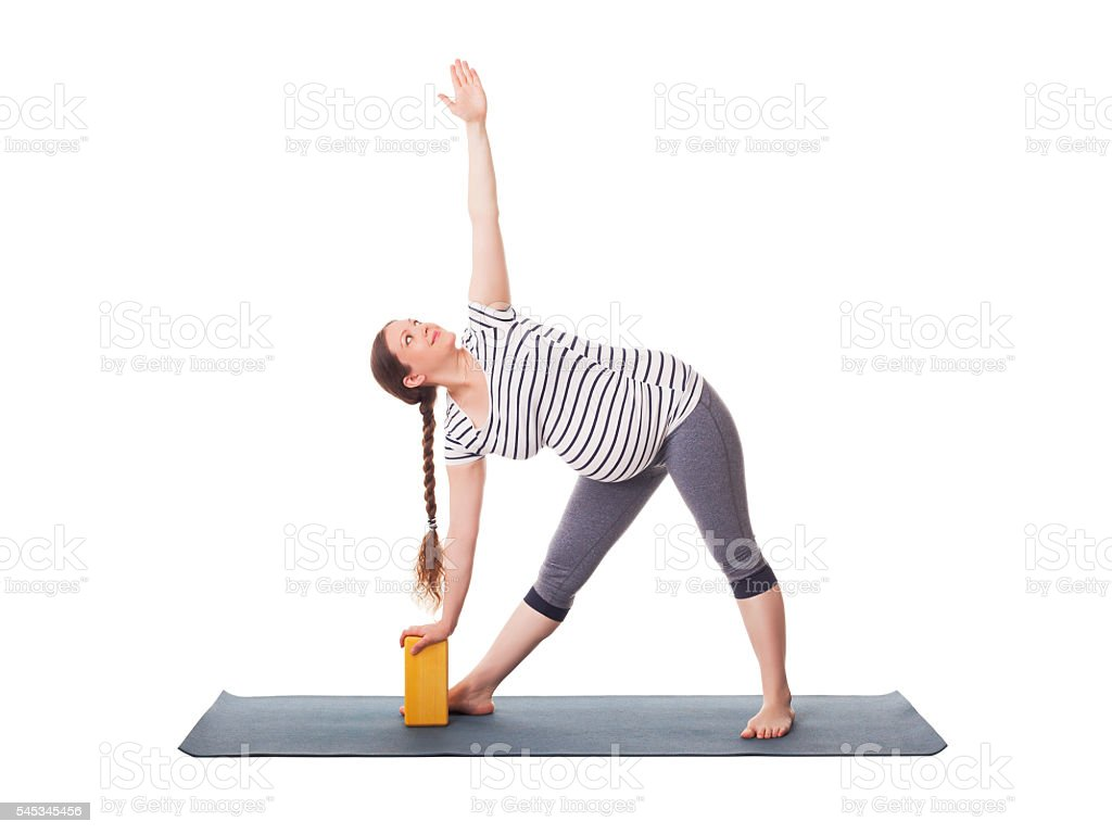Pregnant woman doing yoga asana Utthita trikonasana stock photo