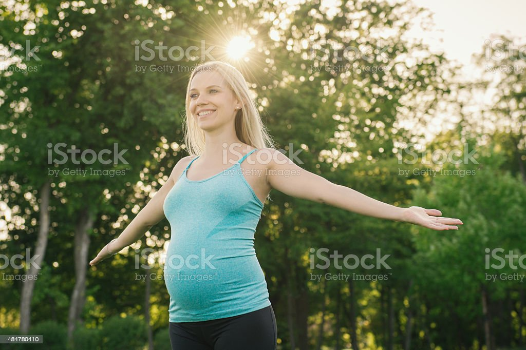 Pregnant woman doing yoga exercises on the nature stock photo