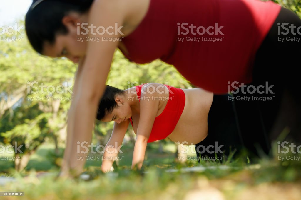 Pregnant Woman Doing Yoga Workout For Backpain Outdoors stock photo