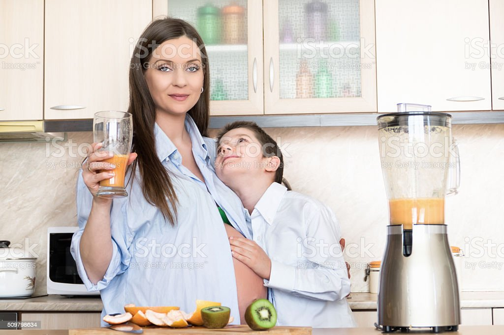 Pregnant woman drinking fresh juice with her son stock photo