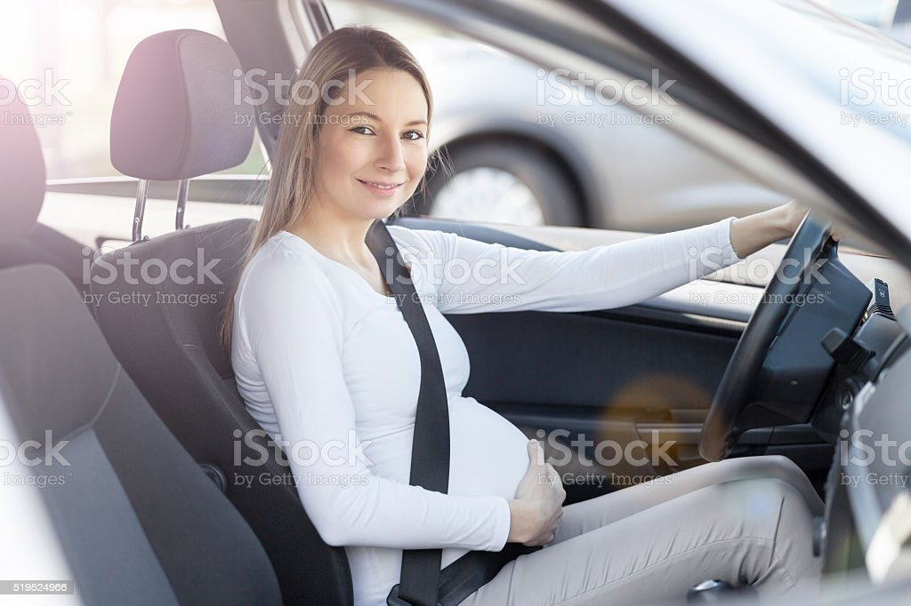 Pregnant woman driving her car stock photo