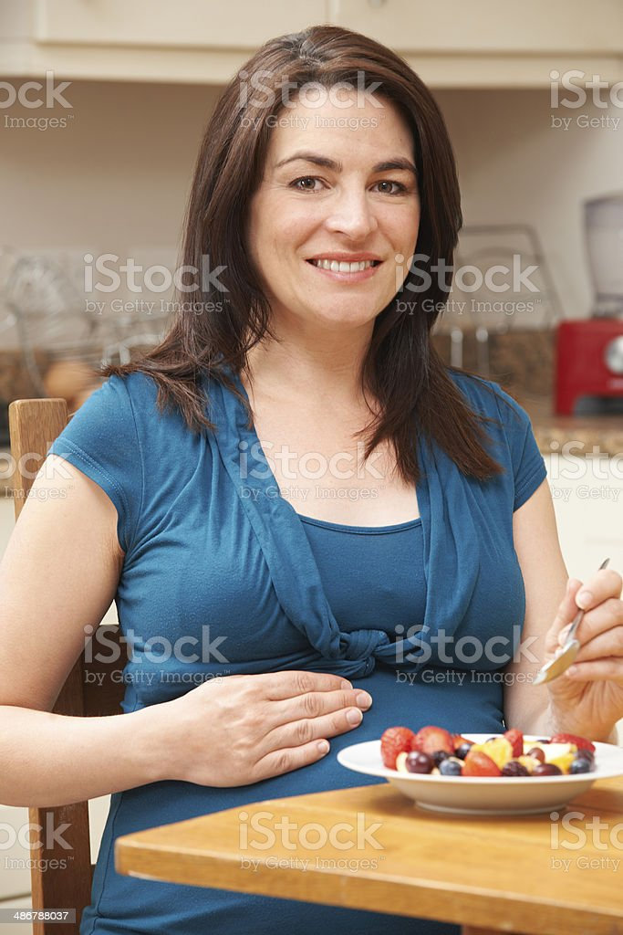 Pregnant Woman Eating Bowl Of Fresh Fruit In Kitchen stock photo
