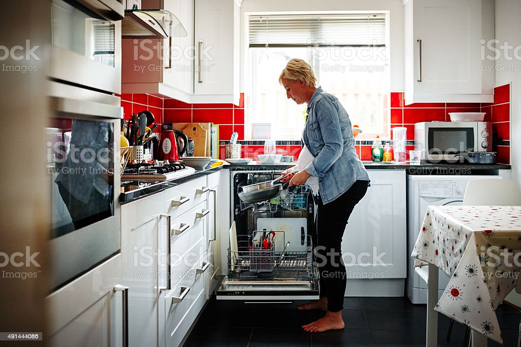 Pregnant woman emptying the dishwasher stock photo