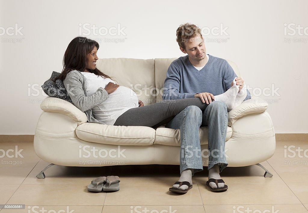 Pregnant woman enjoying foot massage by her husband. stock photo