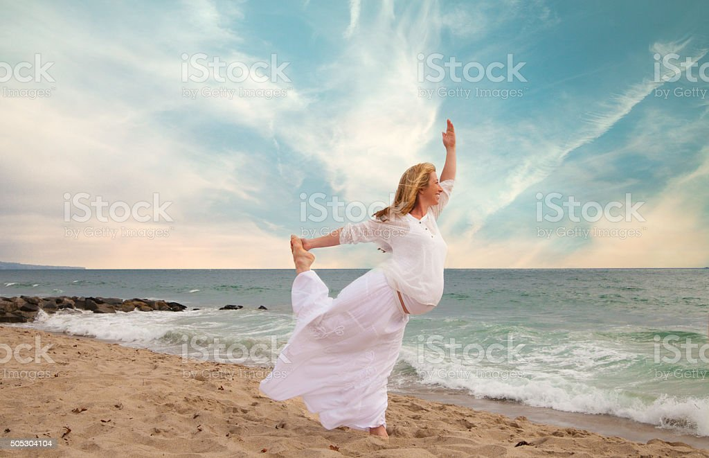 Pregnant woman exercising at the beach stock photo